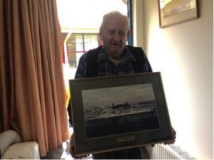 Tony Guest holding a photo of the HMAS Warramunga